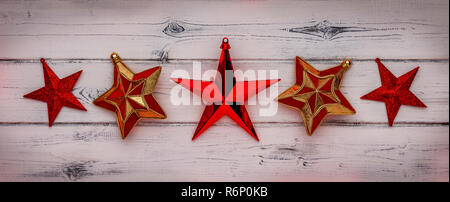 A row of red star christmas decorations, on a distressed white wooden background. - Stock Photo