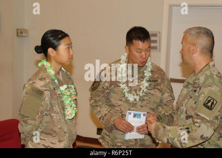 U.S. Army 1st Lt. Yanrong Yang (left), human resource officer, 369th Special Troops Battalion, along with U.S. Army Maj. James Kim (center), chaplain, 369th Sustainment Brigade, discuss the Asian American and Pacific Islander program with Brig. Gen. Stephen Hager, commanding general, 335th Signal Command Theater-Provisional, May 31, Camp Arifjan, Kuwait. Asian Americans and Pacific Islanders concluded the month of May with a heritage dance and celebratory food sampling. - Stock Photo