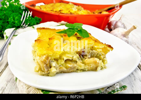 Gratin potato with fish in plate on table - Stock Photo