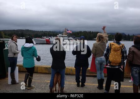 Families await the return of their loved ones stationed aboard the Coast Guard Cutter Bailey Barco (WPC 1122) arriving to its new home port at the moorings of Coast Guard Base Ketchikan during a homecoming ceremony in Ketchikan, Alaska, May 12, 2017. The Fast Response Cutter and its crew completed a 6,200-mile trip from Key West, Florida. U.S. Coast Guard photo. - Stock Photo