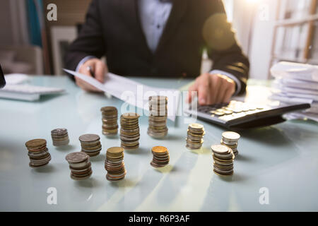 Close-up Of Stacked Coins On Desk - Stock Photo