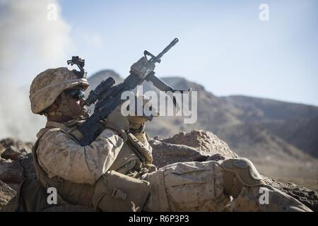 MARINE CORPS AIR GROUND COMBAT CENTER TWENTYNINE PALMS, California – Lance Cpl. Cyrus McCormick, a rifleman with Charlie Company, 1st Battalion, 8th Marine Regiment, reloads his M4A1 assault rifle during a company reinforced assault exercise at Range 400 aboard Marine Corps Air Ground Combat Center, Twentynine Palms, California, May 8, 2017. The Marines conducted a company level assault reinforced by machine guns, vehicles, mortars and snipers as part of Integrated Training Exericse 3-17. ITX is a training evolution conducted five times a year to enhance the lethality and co-operability betwee - Stock Photo