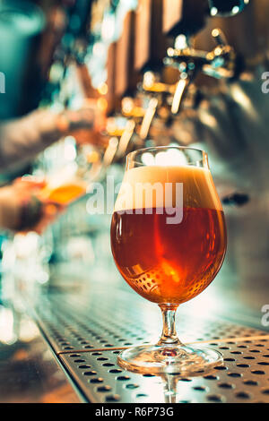 Hand of bartender pouring a large lager beer in tap. - Stock Photo