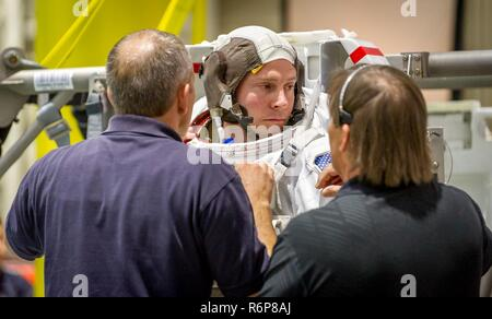 Canadian Space Agency astronaut David Saint Jacques helps Astronaut Col. Tyler N. 'Nick' Hague prepare to be lowered into a pool with a mockup of the International Space Station (ISS) for Extravehicular Activity (EVA) training at the Johnson Space Flight Center's Neutral Buoyancy Laboratory (NBL) in Houston, Tex., Apr. 27, 2017. During  training at NBL, Hague wears a spacesuit to simulate the near weightless environment he will encounter while performing EVAs, or spacewalks, while serving as a flight engineer on Expedition 54/55 aboard ISS in 2018-2019. - Stock Photo