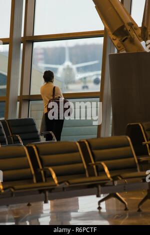 Departure lounge at the airport. A woman standing in front of the window and looking into the distance - Stock Photo