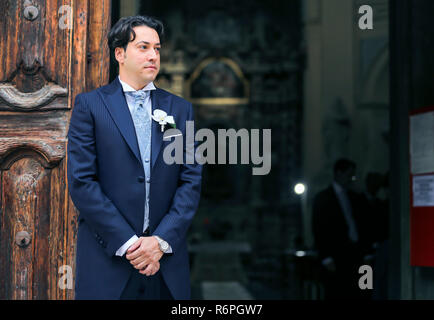 beautiful elegant groom waiting bride near the church - Stock Photo