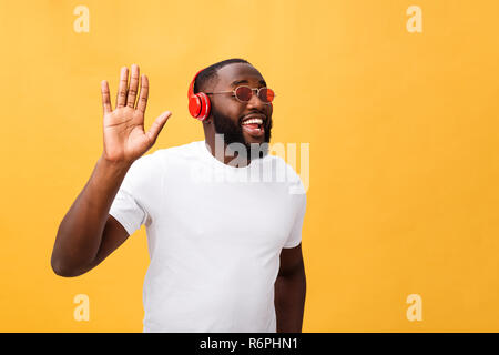 Young African American man wearing headphone and enjoy music over yellow gold Background - Stock Photo