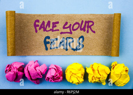 Handwriting text showing Face Your Fears. Concept meaning Challenge Fear Fourage Confidence Brave Bravery written on tear sticky note Paper on the blue background Folded paper - Stock Photo