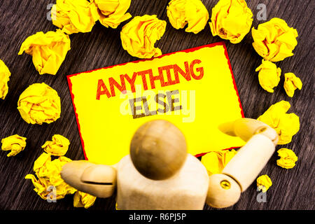 Writing text showing  Anything Else. Business photo showcasing Ask Asking Question to Have Answer written on Sticky Note Holding By Sculpture on the wooden background - Stock Photo