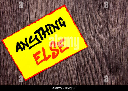 Conceptual hand writing text showing Anything Else. Concept meaning Ask Asking Question to Have Answer written on Yellow Sticky Note Paper on the wooden background. - Stock Photo