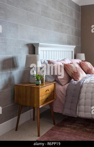 Wooden bedaside cabinet with coral pillows on double bed in Hampshire Mill house redesigned by Emma Painter - Stock Photo