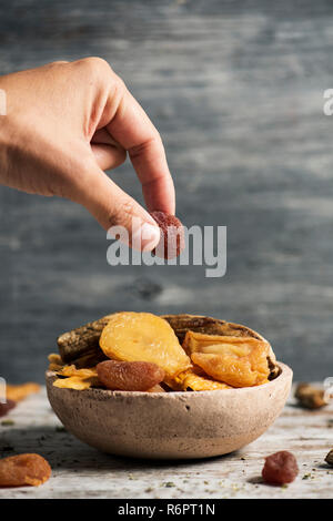 closeup of a young caucasian man taking a dried strawberry from a rustic earthenware bowl full of an assortment of dried fruit, such as pear, peach, b - Stock Photo