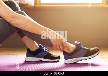 Young woman suffering from an ankle injury while exercising. Sport exercise injuries concept. - Stock Photo