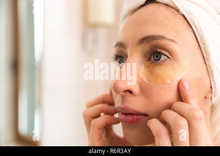 Woman doing facial treatment with eyelid patches at home. Beauty concept - Stock Photo