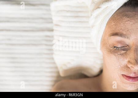 Beautiful young woman having a facial cosmetic treatment with clay face mask. Skin care concept - Stock Photo