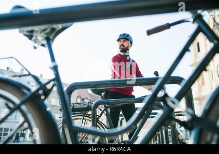 A hipster businessman commuter parking electric bicycle in city when going to work. - Stock Photo