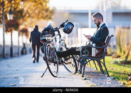 A businessman commuter with bicycle sitting on bench in city and using smartphone when traveling home from work. - Stock Photo