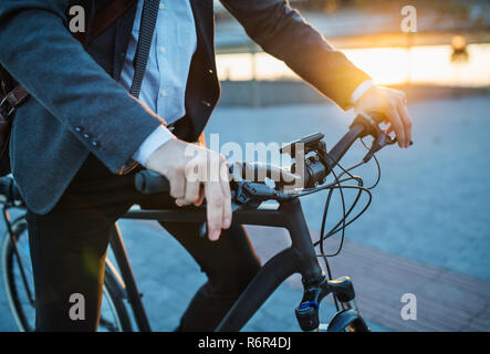 Midsection of businessman commuter with electric bicycle traveling home from work in city. - Stock Photo