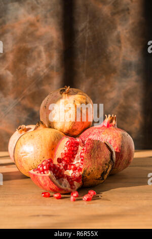 Healthy food concept. Still life with pomegranates on wooden table. - Stock Photo