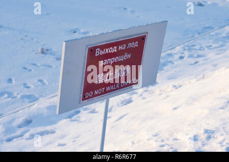Warning information plate with the inscription 'do not walk on ice' in Russian, Chinese and English with footprints on the background - Stock Photo