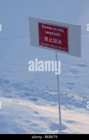 Warning information plate with the inscription 'do not walk on ice' in Russian, Chinese and English - Stock Photo
