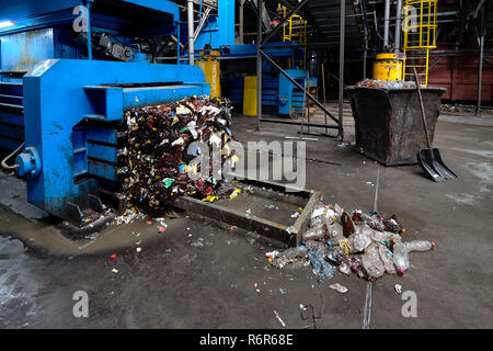 Modern waste sorting and recycling plant, hydraulic press makes wired bale from pressed PET bottles for processing and reuse of plastic. Concept of en - Stock Photo