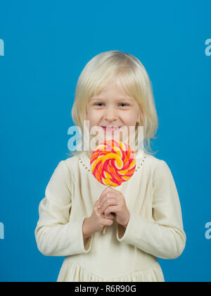 Bold hard candy creation. Small child with sweet lollipop. Small girl hold lollipop on stick. Happy candy girl. Happy childhood food - Stock Photo