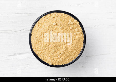 Ginger powder in round cast iron bowl on white wooden background, view directly from above - Stock Photo