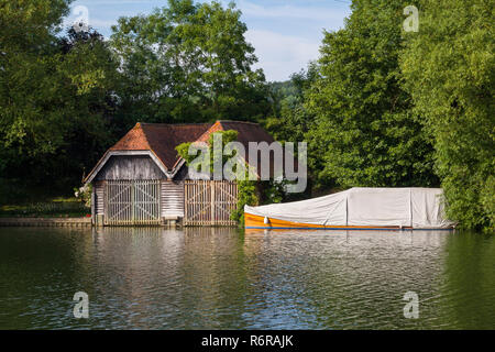 An old boathouse and classic mahogany launch under a canvas cover on the Thames at Mill End, Buckinghamshire - Stock Photo