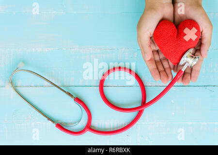 World health day, Healthcare and medical concept. Woman hand holding red heart with Stethoscope, notepad or notebook, thermometer and yellow Pill on Pastel white and blue wooden table background texture. - Stock Photo