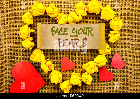 Handwriting Announcement text showing Face Your Fears. Concept meaning Challenge Fear Fourage Confidence Brave Bravery written on Sticky Note Paper With Heart on the textured background - Stock Photo
