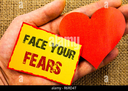 Handwriting text showing Face Your Fears. Business concept for Challenge Fear Fourage Confidence Brave Bravery written on Sticky Note Paper With Heart Holding Hand with Finger. - Stock Photo