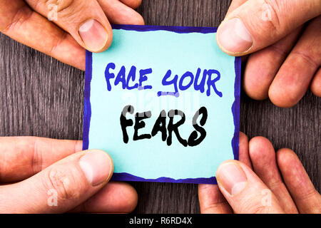 Handwriting Announcement text showing Face Your Fears. Conceptual photo Challenge Fear Fourage Confidence Brave Bravery written on Sticky Note Paper Holding Hand with Finger. - Stock Photo