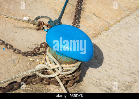 mooring rope of a little ship in the port. Mooring rope and bollard on sea water - Stock Photo