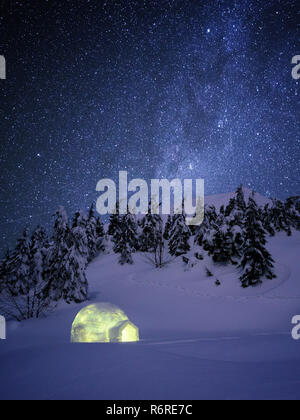 Night wonderland in winter. Igloo snow in the fir forest under a starry sky. Shelter in a mountain winter hike - Stock Photo