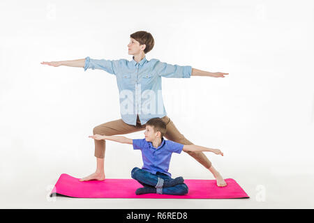 mother and son doing yoga, spending a good time together . isolated on white. - Stock Photo