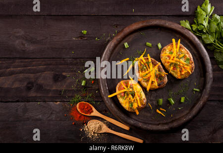 Baked stuffed potatoes with cheese, bacon, chives, dill and spices on dark background. Top view. - Stock Photo