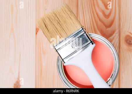 Brush on open can of Living Coral color of paint on natural wooden board. Renovation concept. - Stock Photo