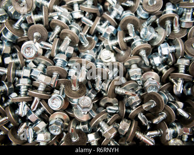 A scattering of roofing screws with a hexagon head - Stock Photo