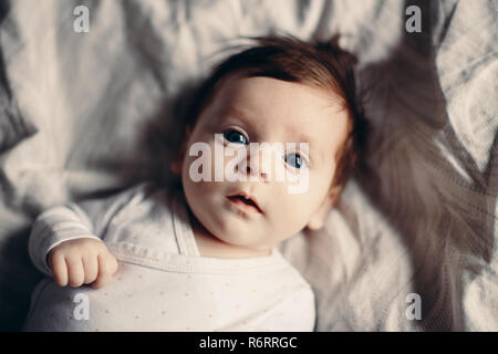 Closeup portrait of cute adorable funny white Caucasian brunette little baby newborn with blue grey eyes lying on bed looking in camera. Authentic lif
