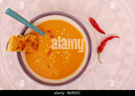 Lentil soup in bowl with fresh baked corn bread and red hot chilli peppers on cloth fabric view from above - Stock Photo