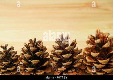 Natural dry pine cones lined up on light brown wooden background with free space for text and design - Stock Photo