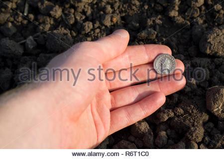 Hand holding Roman denarius (Roman silver coin) - Stock Photo