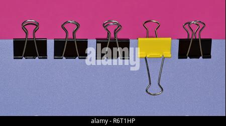 A side view of a line of black binder clips with a single yellow one to break up the conformity. Clips are attached to a purple folder. - Stock Photo