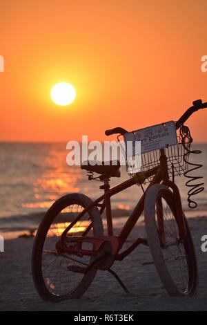 Bicycle on Tarpon Beach at sunset on Sanibel Island, Florida - Stock Photo