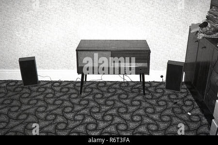 1970s, wooden record or music cabinet with in-builtspeaker in a corner of a room, with two additional speakers on the floor of a patterned carpet, Englad, UK.