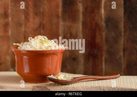 Brown clay pot and wooden spoon with sauerkraut are standing on wooden board against old wooden wall. - Stock Photo