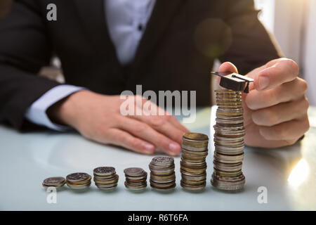 Businessperson Placing Graduation Hat On Top Of Stacked Coins - Stock Photo