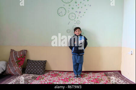 06 December 2018, Afghanistan, Kabul: Murtasa Ahmadi is in a room. Two years ago, the little football fan Murtasa Ahmadi from Afghanistan was a worldwide star on the Internet with his homemade Messi jersey. Now the now seven-year-old boy and admirer of the Argentine footballer Lionel Messi fled with his family from his home district Dschaguri to the capital Kabul. (to dpa: 'Little Messi-fan escaped from Taliban to Kabul' from 06.12.2018) Photo: Veronika Eschbacher/dpa - Stock Photo