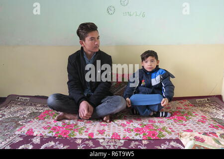 06 December 2018, Afghanistan, Kabul: Murtasa Ahmadi (r) sits in a room next to his brother Humayun. Two years ago, the little football fan Murtasa Ahmadi from Afghanistan was a worldwide star on the Internet with his homemade Messi jersey. Now the now seven-year-old boy and admirer of the Argentine footballer Lionel Messi fled with his family from his home district Dschaguri to the capital Kabul. (to dpa: 'Little Messi-fan escaped from Taliban to Kabul' from 06.12.2018) Photo: Veronika Eschbacher/dpa - Stock Photo